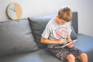 Child sitting on sofa with tablet